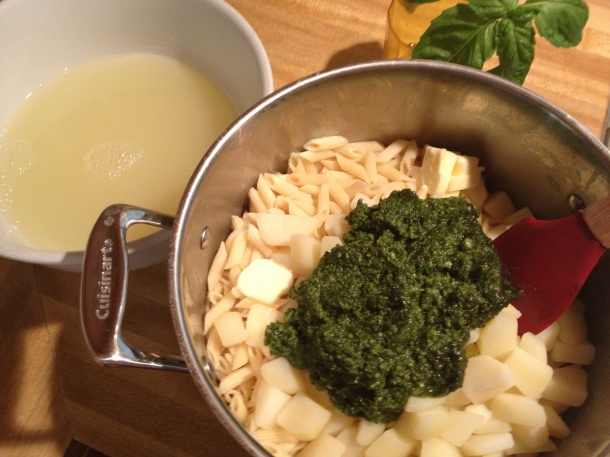 Pasta, potatoes, pasta water, butter and pesto ready to be beaten together