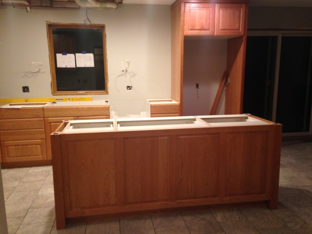 Island with frig cabinet in back. Lower cabinets installed below window