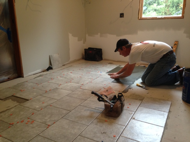 Terry laying the tiles over the cement board, cementing each tile in place.