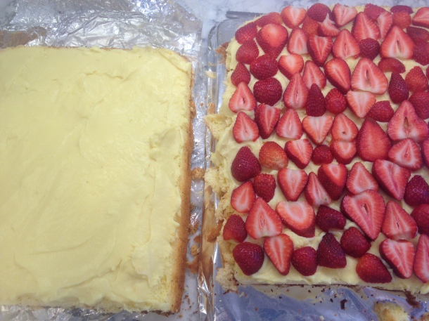 Cake sliced in half and spread with custard and covered with fresh strawberries